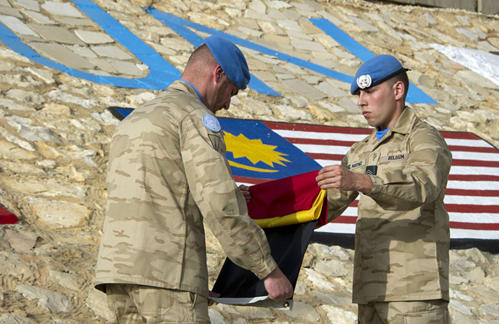Belgian peacekeepers take down and fold the Belgian flag at the end of the ceremony.